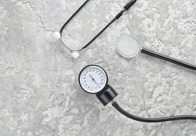 Kardiologische medizinische geräte zur druckmessung auf einer betonoberfläche. stethoskop und messgerät. draufsicht.