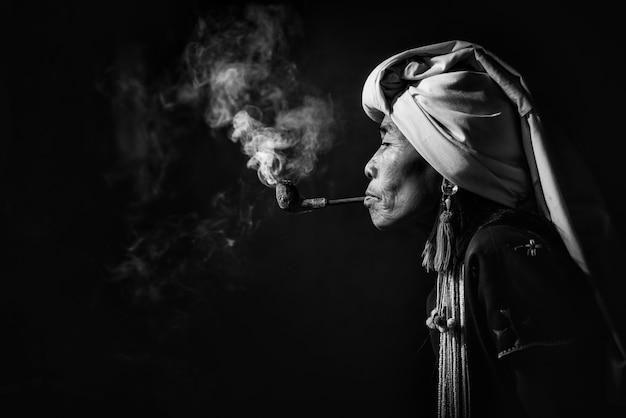 Karen-stammesfrau, die opium mit einem rohr nahe chiangmai, thailand raucht.