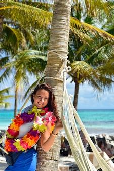 Karibik-urlaubsmädchen lehnt sich an palme und trägt florale halskette