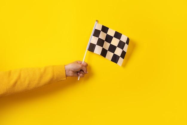 Karierte flagge in der hand über gelbem hintergrund