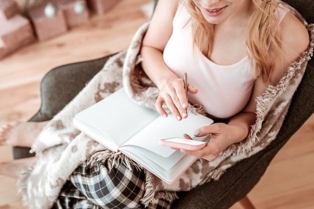 Karierte pyjamahose. langhaarige frau im haushaltsoutfit, die beim füllen des leeren tagebuchs mit einer decke bedeckt ist