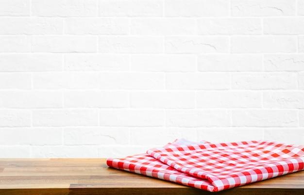 Karierte tischdecke auf holz mit unscharfem weißem backsteinmauer-küchenhintergrund. für wichtige visuelle lebensmittel- und getränkeprodukte.