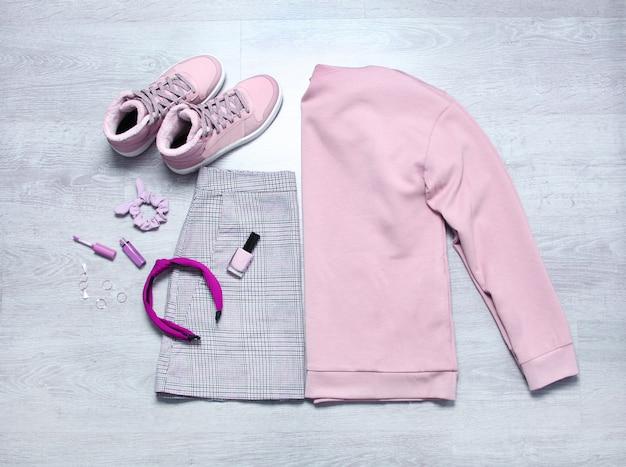 Karierter rock, rosa sweatshirt, rosa turnschuhe, nagellack, lipgloss und accessoires