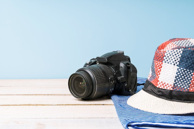 Karierter sommerhut und kamera auf weißem holztisch