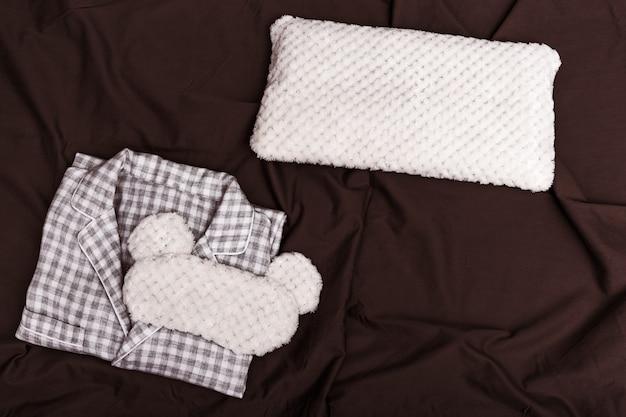 Karierter warmer pyjama für frauen, weiches kissen und augenmaske zum schlafen auf dunklem laken auf dem bett. draufsicht. flach liegen.