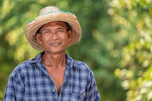 Kariertes hemd der asiatischen landwirtabnutzung glücklich im garten