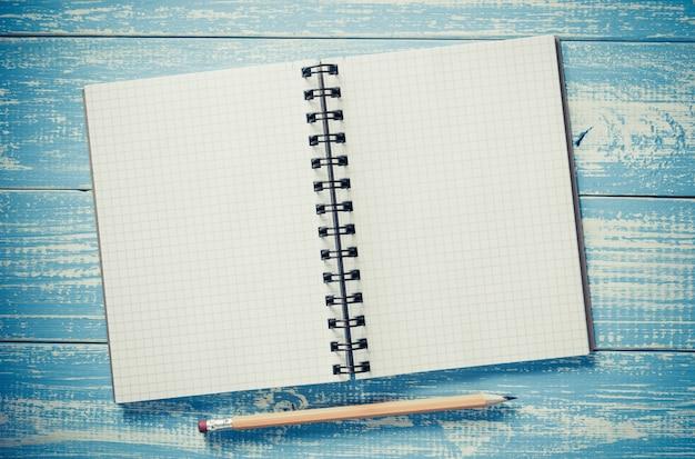 Kariertes notizbuch auf holztisch