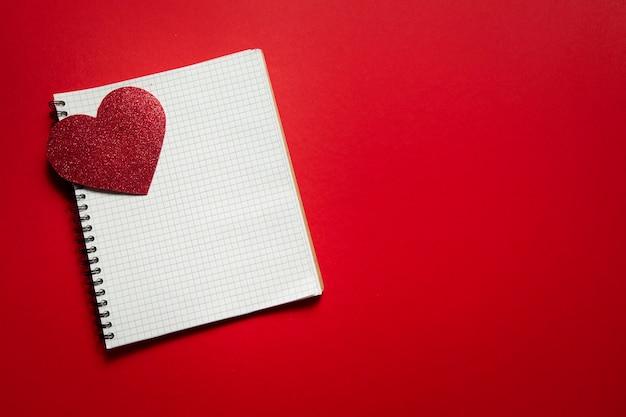 Kariertes notizbuch mit valentinstagherz auf rotem hintergrund