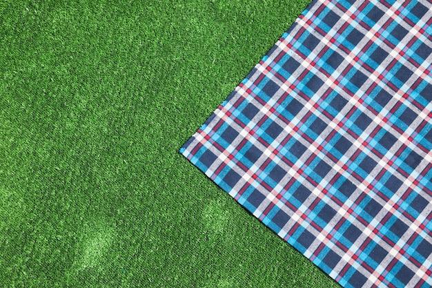 Kariertes tischtuch auf grünem rasen