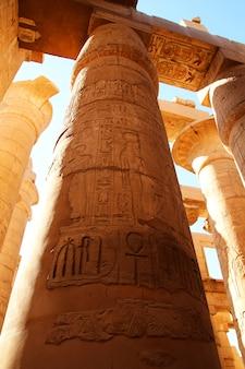 Karnak tempelkomplex in luxor. mehrfarbige säulen mit schnitzereien des pharaos und seiner frau