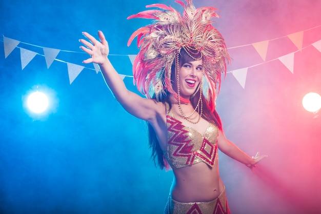 Karneval, bauchtanz und feiertagskonzept - schöne samba-tänzerin, die goldkostüm trägt und lächelt.