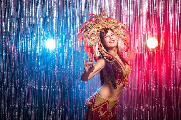 Karneval, tänzerin und urlaubskonzept - beauty brunette frau im kabarettanzug und kopfschmuck mit natürlichen federn und strasssteinen.