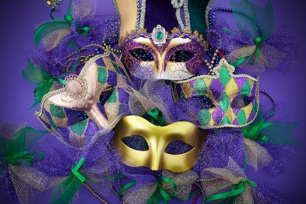 Karneval-, venezianische oder karnevalsmaske auf einem lila hintergrund. draufsicht