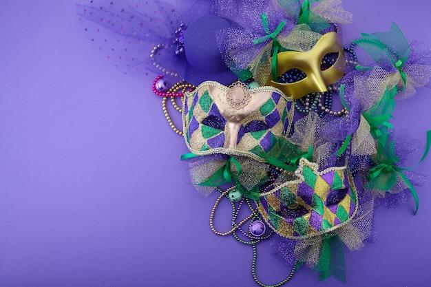 Karneval, venezianische oder karnevalsmaske auf einem lila hintergrund mit kopienraum für text. draufsicht