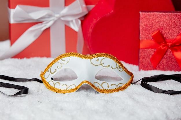Karnevalsmaske auf dem schnee nahe geschenkboxen