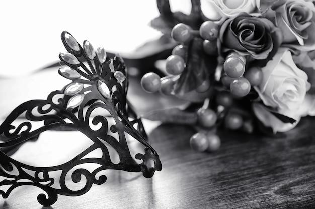 Karnevalsmaske auf dem tisch. das thema tarnung beim date während eines karnevals. venezianische maske auf einem holztisch in schwarz und weiß.