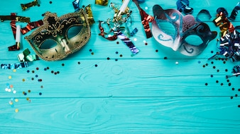 Karnevalsmaske mit zwei Maskeraden mit Parteidekorationen über blauem Holztisch