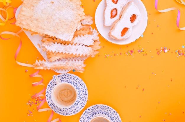 Karnevalsmaske, zwei tassen aromatischen kaffee, süßigkeiten und konfetti auf gelbem grund. dekor für einen traditionellen italienischen feiertag. speicherplatz kopieren. flach liegen