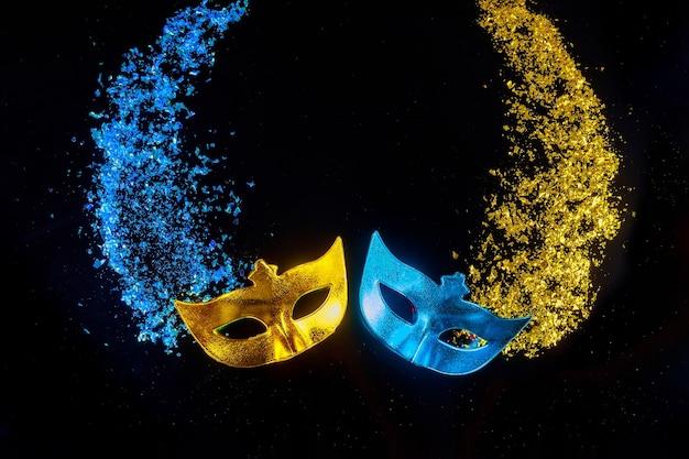 Karnevalsmasken auf schwarzem hintergrund. jüdischer feiertag purim.