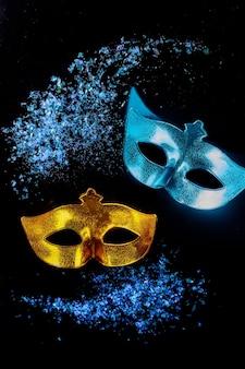 Karnevalsmasken auf schwarzem hintergrund jüdischer feiertag purim.