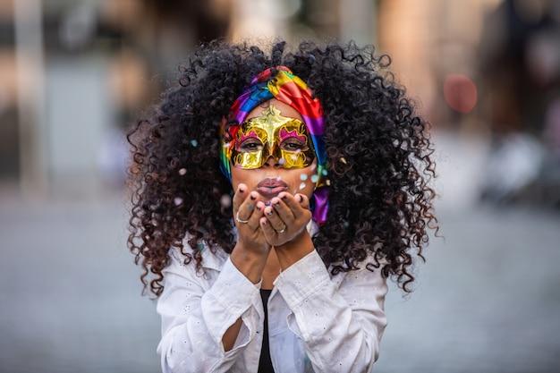 Karnevalsparty. brasilianische frau des lockigen haares im kostüm, das konfetti bläst