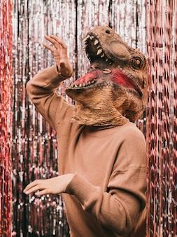 Karnevalsparty mit verspieltem dinosaurierkostüm