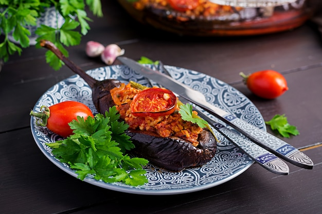Karniyarik - türkische traditionelle auberginenmahlzeit. gefüllte auberginen mit rinderhackfleisch und gemüse mit tomatensauce gebacken