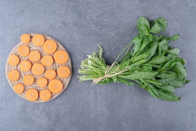 Karotte auf einem untersetzer neben dem grün auf der marmoroberfläche geschnitten.