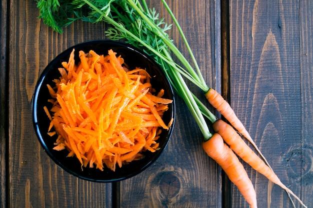 Karotte gerieben in einer schüssel, auf einem holztisch.