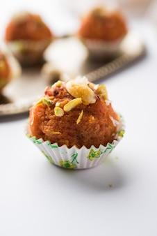 Karotte halwa laddu oder süße kugeln, serviert in einem teller mit trockenfrüchten. selektiver fokus