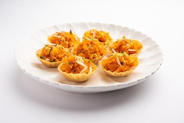 Karotte oder gajar halwa canape oder canapé oder fusion tart, garniert mit trockenfrüchten. indisches dessert
