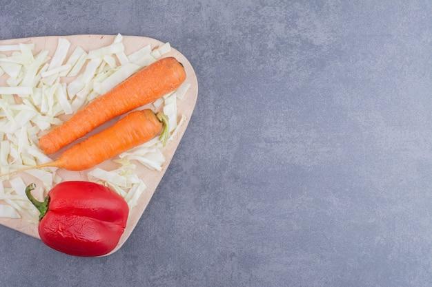 Karotte, rote chilischote und kohl auf einer holzplatte