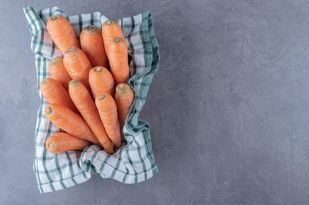 Karotten auf einem handtuch in der schachtel, auf der marmoroberfläche.