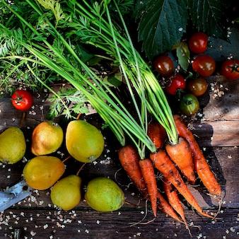 Karotten, birnen, tomaten, hölzerner hintergrund, garten, herbst