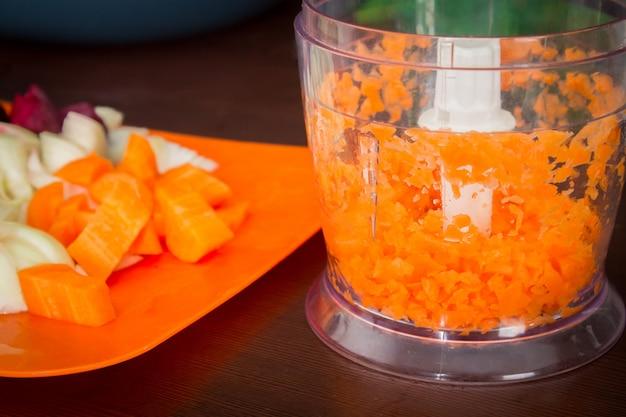 Karotten für borschtsch in einem elektrischen häcksler. suppe kochen.
