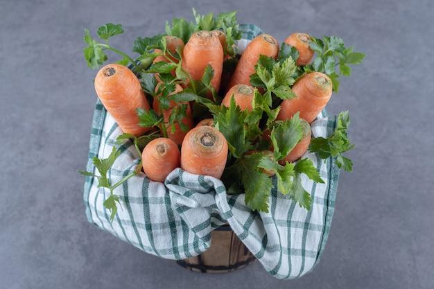 Karotten mit blättern auf dem handtuch im eimer, auf der marmoroberfläche.
