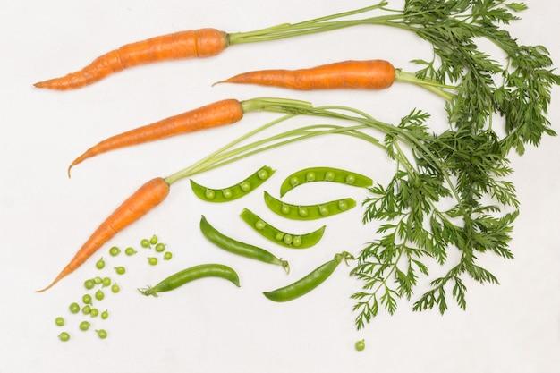Karotten mit tops, grüne erbsenschoten auf dem tisch.