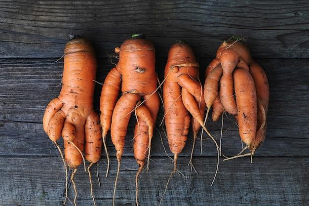 Karotten mit verdrehten wurzeln auf holztisch