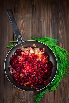 Karotten, rote rüben und zwiebeln in einer bratpfanne, um dill, auf einem braunen hölzernen hintergrund.