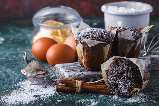 Karotten-schokoladen-muffins mit puderzucker bestäubt, eine tasse tee, backzutaten. mehl, eier, zitrone zitrusfrüchte auf einem dunklen tisch