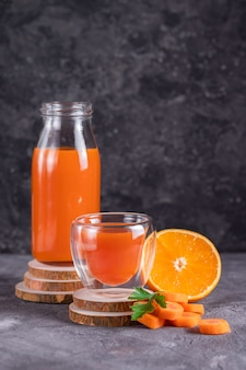 Karotten- und orangensaft in einer flasche und glas auf holzständern in einem zurückhaltenden
