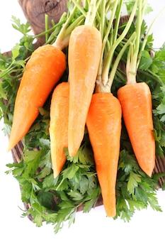 Karotten und petersilie auf schneidebrett lokalisiert auf weiß