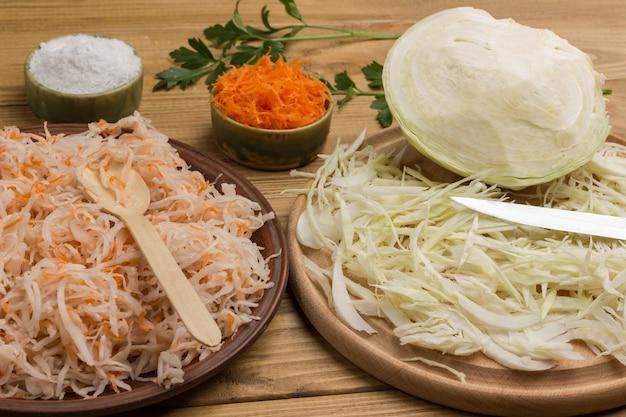Karotten und salzkohl in teller. geschnittener rohkohl, messer auf schneidebrett. hausgemachte fermentationsprodukte. nahansicht