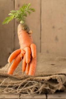 Karotten von ungewöhnlicher form liegen auf einem holztisch