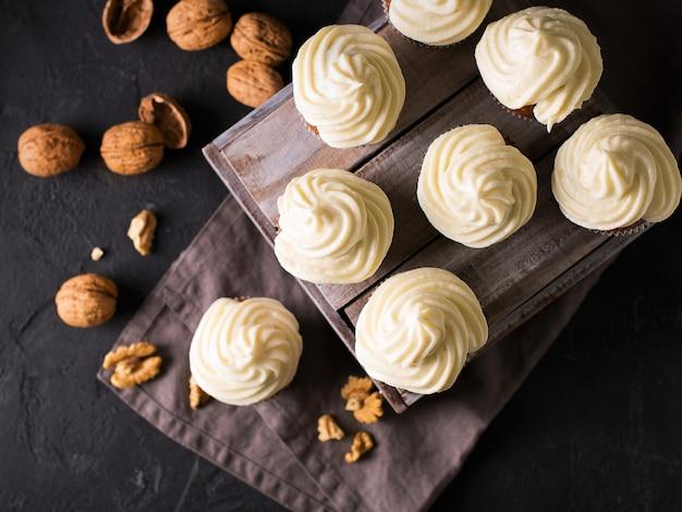 Karottencupcakes oder -muffins mit nüssen auf schwarz