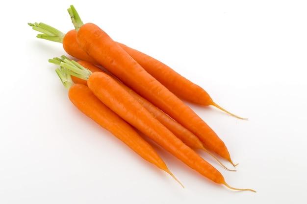 Karottengemüse mit blättern auf weißem holztisch.