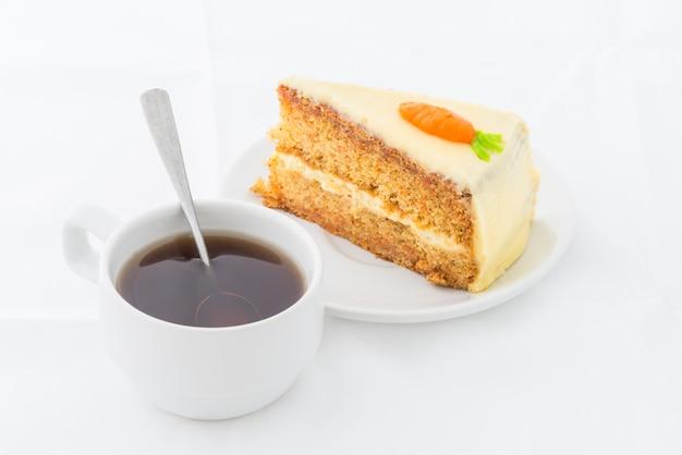 Karottenkuchen auf weißem teller mit heißem getränk