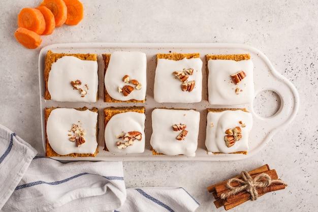 Karottenkuchen des strengen vegetariers mit kokosnusscreme und pekannuss, pflanzliches diätkonzept, draufsicht.