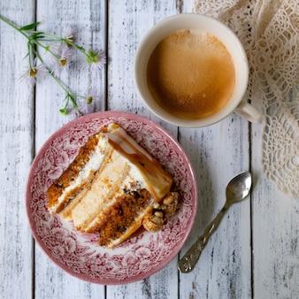 Karottenkuchen mit gesalzenem karamell und käsekuchen innen, dekoriert mit popcorn und karamell. ein stück kuchen mit einer tasse kaffee, retro-stil, vintage.