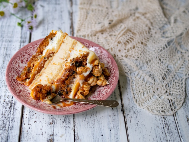 Karottenkuchen mit gesalzenem karamell und käsekuchen innen, dekoriert mit popcorn und karamell. ein stück kuchen, retro-stil, vintage.